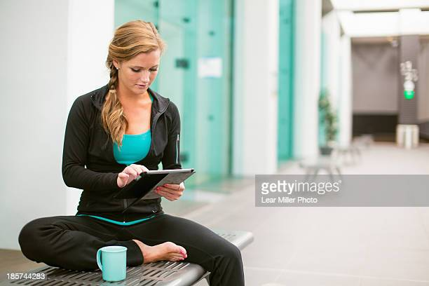 Young woman in gym corridor using digital tablet