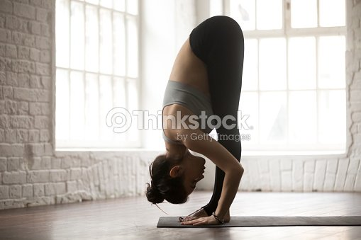 Young Woman In Head To Knees Exercise White Loft Studio Stock Photo