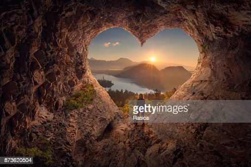 Young woman in heart shape cave towards the idyllic sunrise : Stock Photo