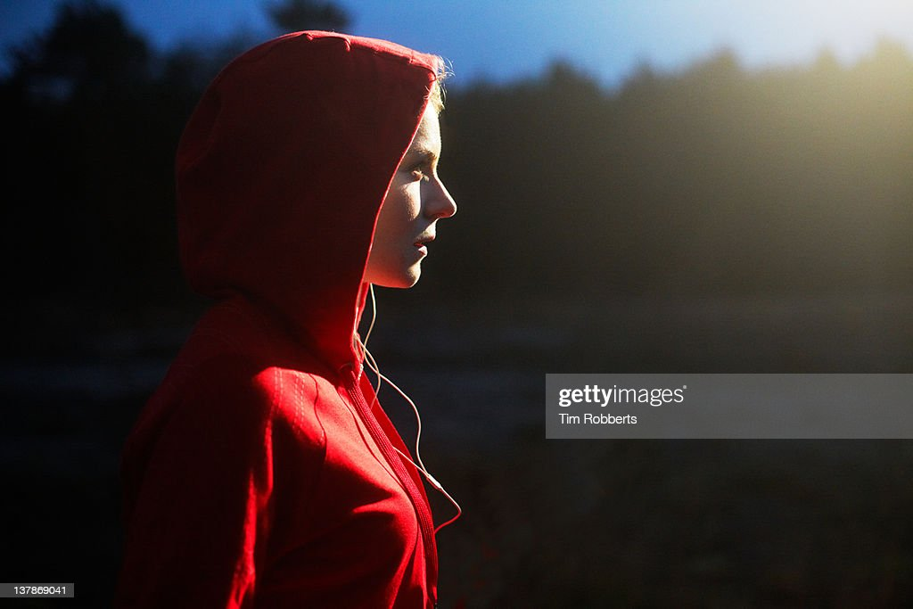 Young woman in hooded top listening to music.