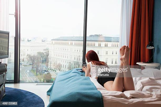 Young woman in hotel room overlooking street