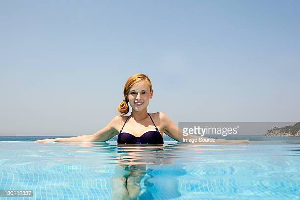 Young woman in infinity pool, looking at camera