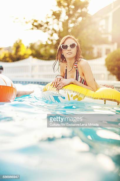 Young woman in inflatable lounger at pool party