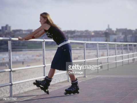 Young woman in inline skate leaning on railing : Stock Photo