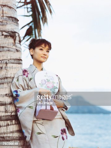 Young woman in Japanese kimono leaning on coconut tree, portrait : Stock Photo