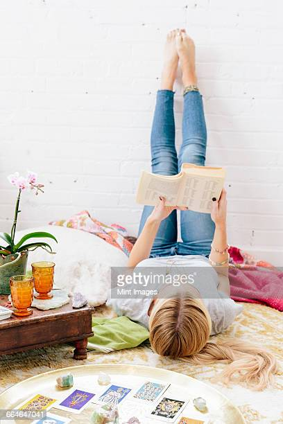 A young woman in jeans lying on her back with her legs against the wall.