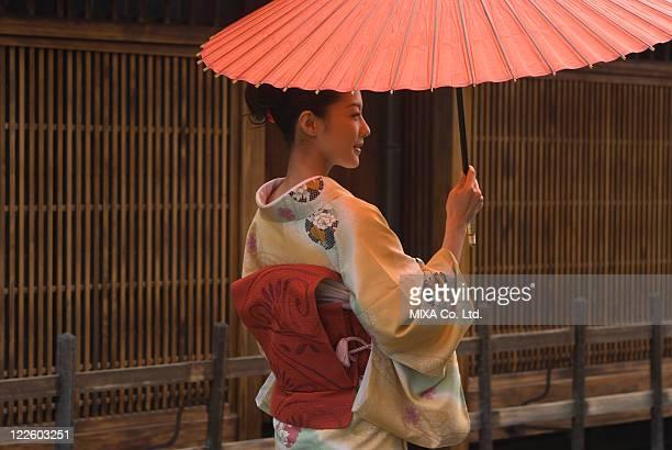Young woman in kimono holding paper umbrella