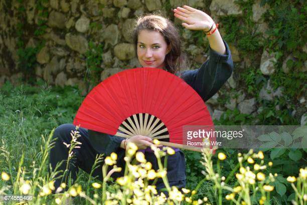 Young woman in kimono holding red fan