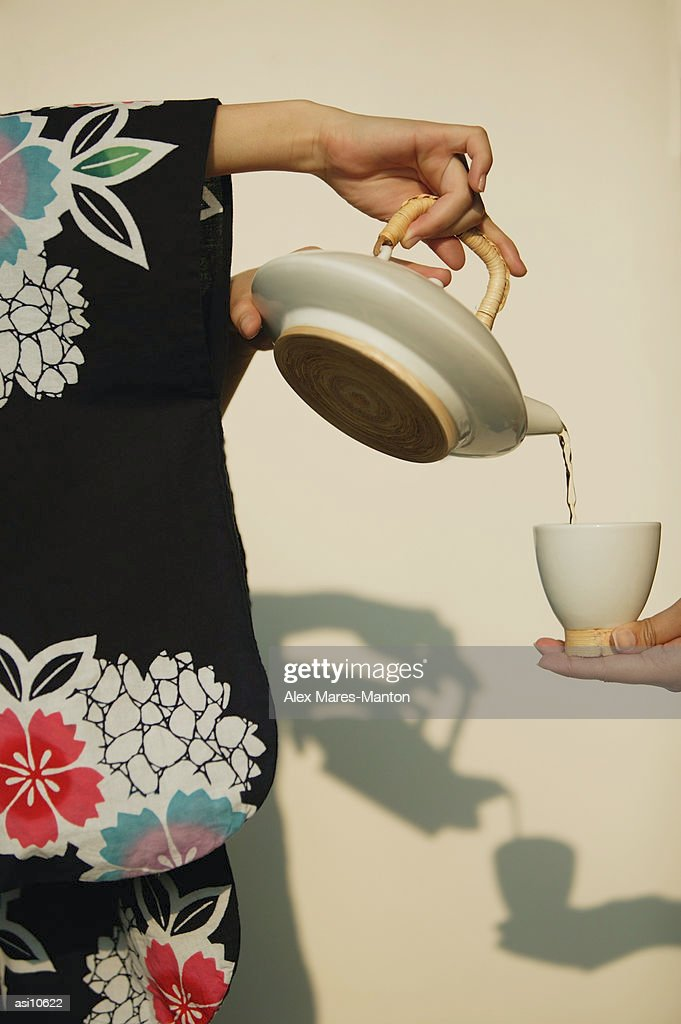 Young woman in kimono pouring tea for someone. : Stock Photo