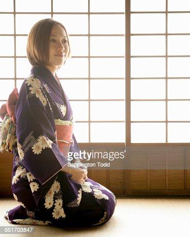 Young Woman In Kimono Sitting On Tatami