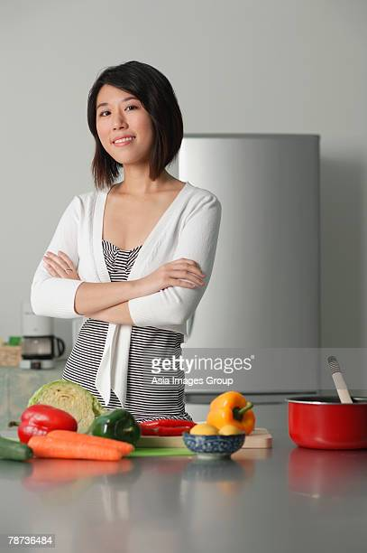 Young woman in kitchen, arms crossed, vegetables on the table in front of her