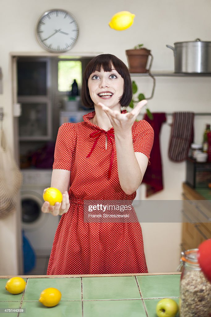 Young woman in kitchen juggling lemons