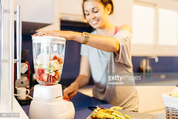 Young woman in kitchen preparing a healthy drink in blender