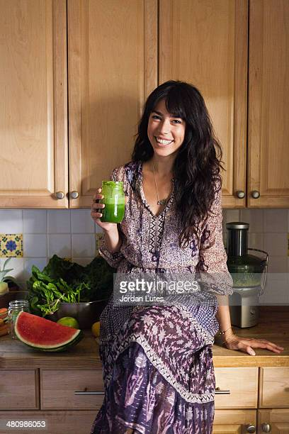 Young woman in kitchen with vegetable juice