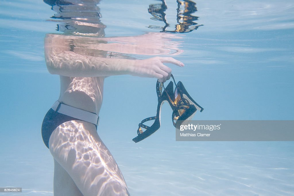 Young woman in lagoon holding black high heels : Stock Photo