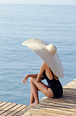 Young woman in large hat sitting on jetty
