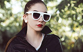 Pierced young woman in leather jacket wearing sunglasses