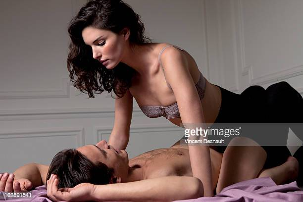 Young woman in lingerie astride a man