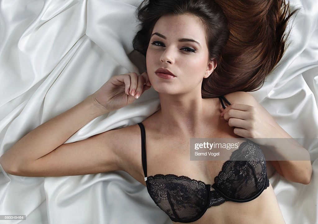 Young woman in lingerie lying on silk blanket