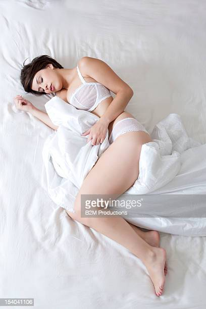 Young Woman In Lingerie Sleeping On Bed
