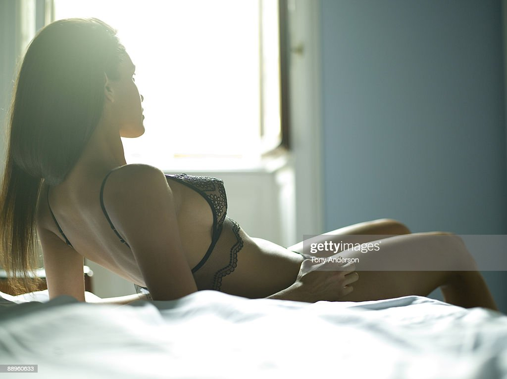 Young woman in lingerie waiting in bed : Stock Photo