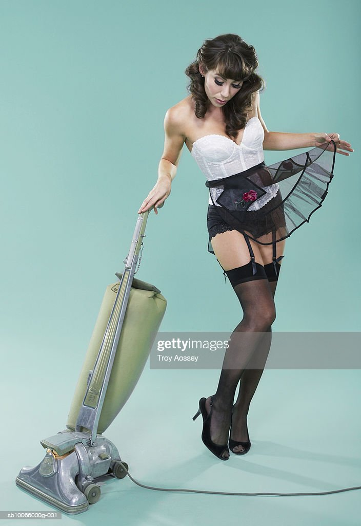 Young woman in lingerie with vacuum cleaner : Stock Photo