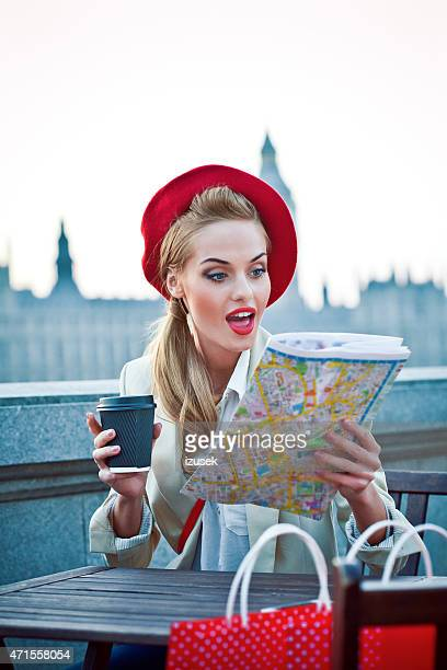 Young woman in London at sunset watching map