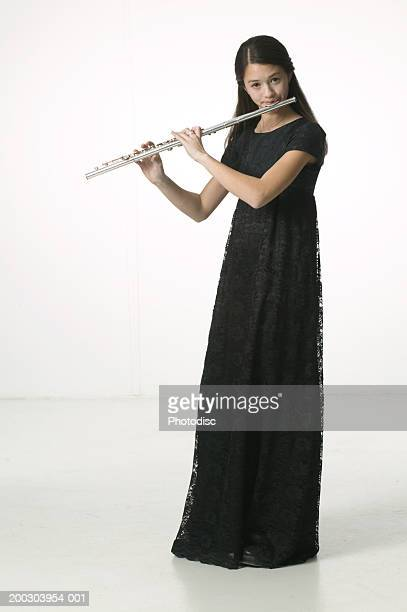 Young woman in long black dress, playing flute in studio, portrait