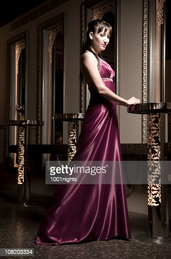 Young Woman in Long Dress Resting Hands on Nightclub Table