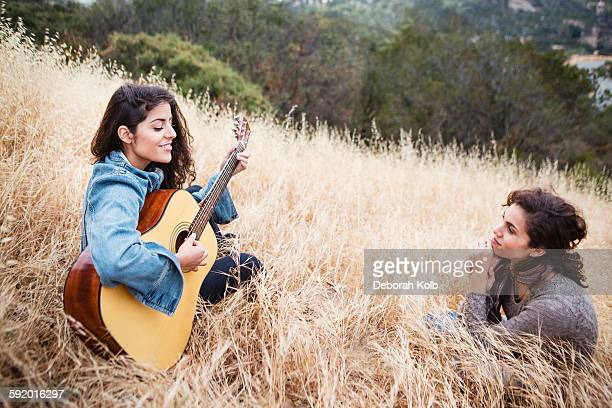 Young woman in long grass playing guitar to friend, Woodland Hills, California, USA