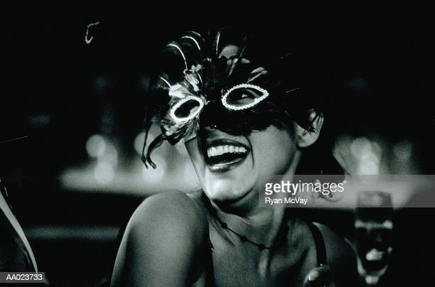 Young woman in masquerade laughing, close-up (B&W)