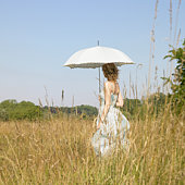 Young woman in meadow holding parasol.