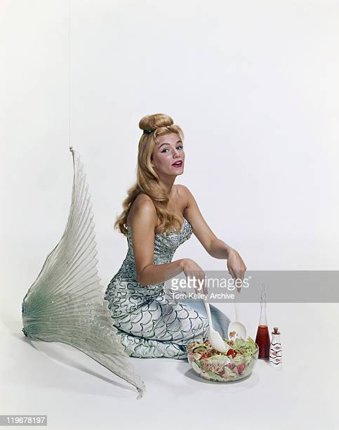 Young woman in mermaid costume making salad, portrait