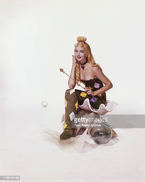 Young woman in mermaid costume sitting on shell, smiling, portrait