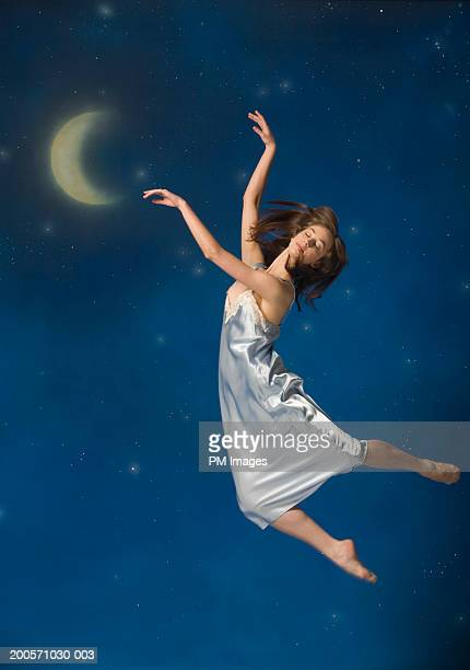 Young woman in mid-air, eyes closed