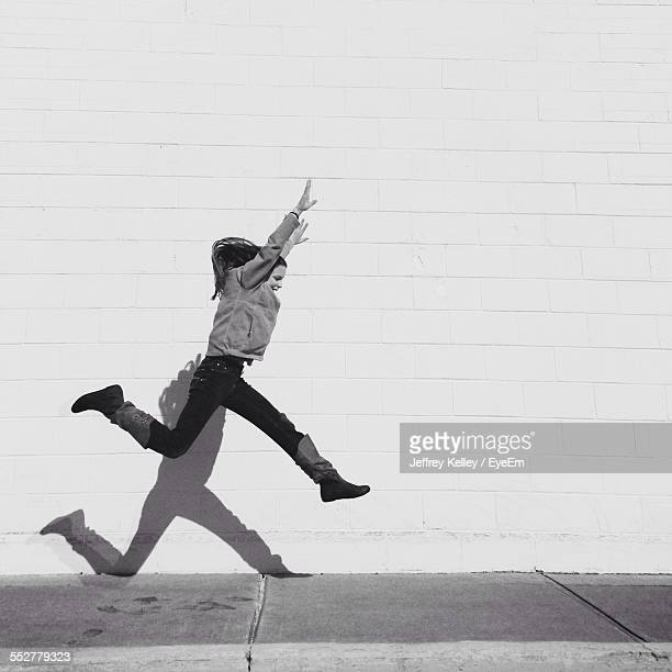 Young Woman In Mid-Air Over Sidewalk Against Wall