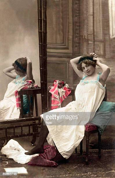 Young woman in negligee near a mirror postcard 10's