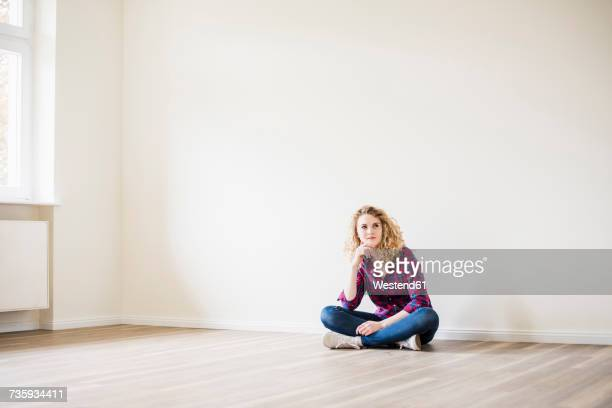 Young woman in new home sitting on floor