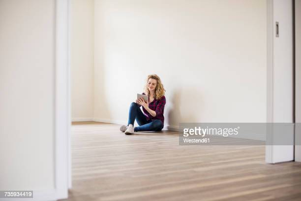 Young woman in new home sitting on floor using tablet
