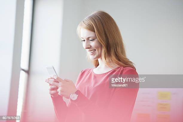 Young woman in office using smartphone