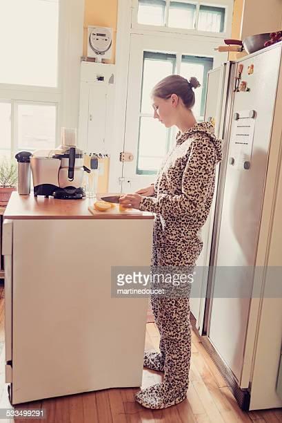 Junge Frau in Strampelanzug mit einem Saftpresse in kleine Küche.