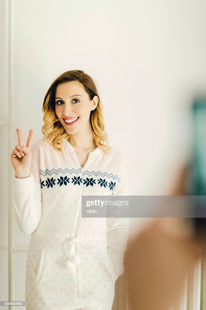 Young Woman In Onesie With Peace Sign At Home. : Stock Photo