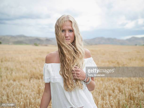 Young woman in open field under stormy skies