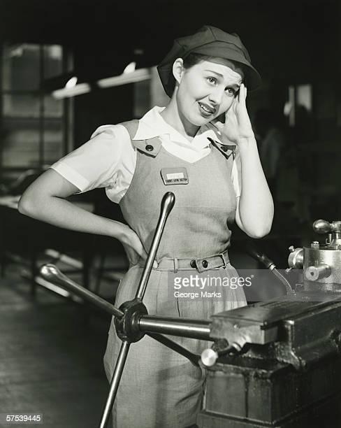 Mujer joven en monos de montaje en torno de fábrica, (B & P