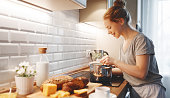 young woman in pajamas prepares breakfast in the morning