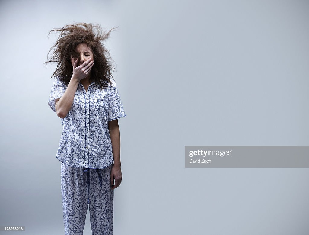 Young woman in pajamas, yawning