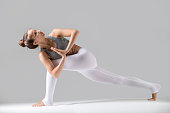 Young attractive woman practicing yoga, standing in Revolved Side Angle exercise, Parivrtta Parsvakonasana pose, namaste, working out wearing sportswear, indoor full length, grey studio background