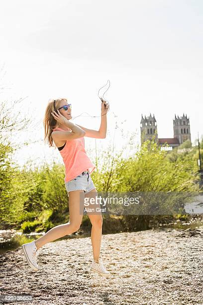 Young woman in park dancing whilst listening to headphones