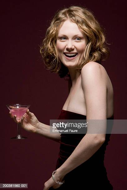 Young woman in party dress holding cocktail, laughing