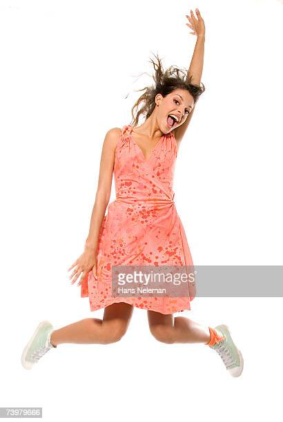 Young woman in pink dress and white tennis shoes jumping into air